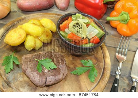 Ostrich Steaks With Baked Potatoes And Vegetables