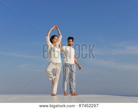 young couple practicing yoga at sunset in modern home terace with ocean and sunset in background poster