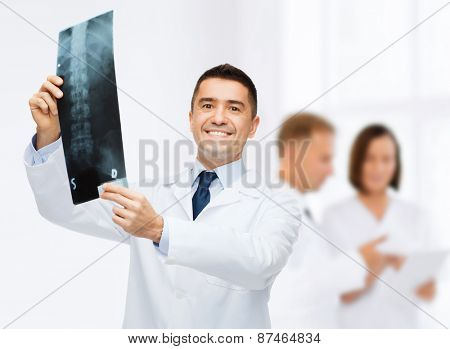 healthcare, rontgen, people and medicine concept - smiling male doctor in white coat with x-ray over group of medics at hospital background