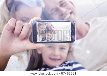 Hand holding smartphone showing against happy parent tickling her cute son on the couch