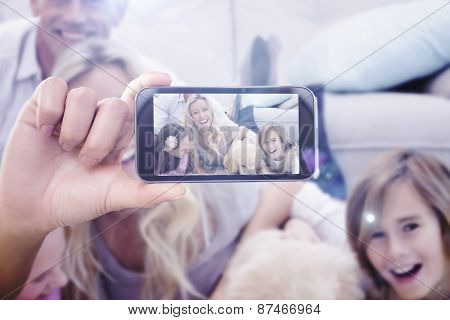 Hand holding smartphone showing against laughting family with their pet yellow labrador on the rug
