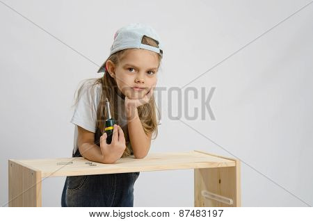 Girl-collector Of Furniture With A Screwdriver Wearily Leaned On The Cabinet