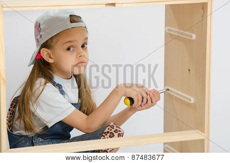 Girl-collector Of Furniture With A Screwdriver Collects Wooden Cabinet