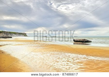 Arromanches Les Bains, Normandy, France. Seafront Beach And Remains Of The Artificial Harbor