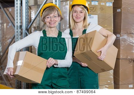 Smiling female storage workers holding cardboard boxes poster
