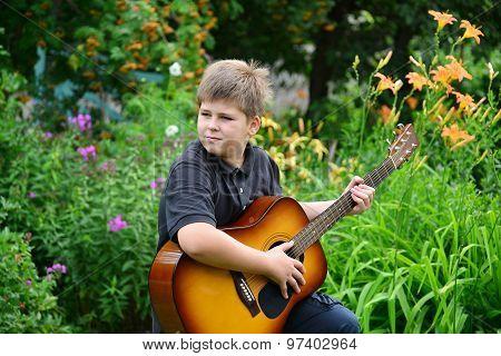 Teen Boy Playing Guitar Outdoor In A Summer