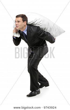 Full Length Portrait Of A Businessman Carrying A Money Bag