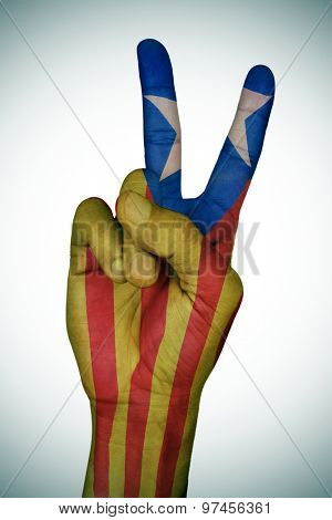 the hand of a young man giving the V sign patterned with the Estelada, the Catalan pro-independence flag