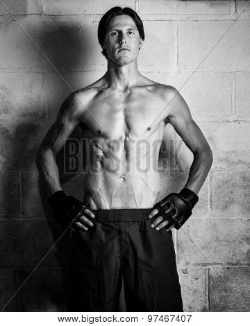 Young adult martial artist in front of a concrete block wall. Black and white.