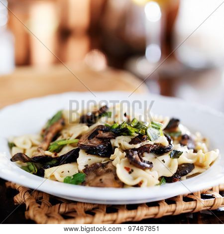bow tie pasta with mushrooms and basil shot close up on white plate