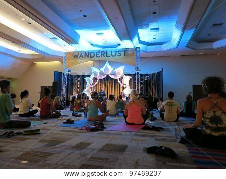 Author And Teacher Max Storm Teaches Yoga Class From A Stage To A Room Filled With Students Indoors