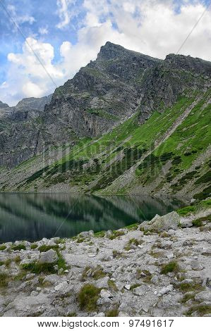 Crystal Clear Lake With Refection Of Surrounding Mountain Range