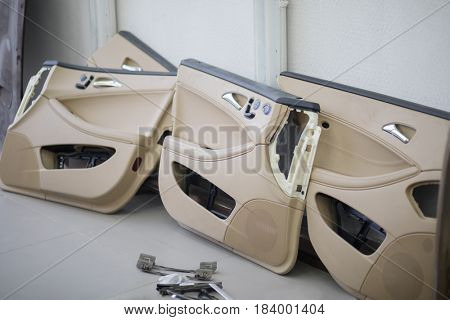 Four doors of modern car and instruments are on floor in empty car service