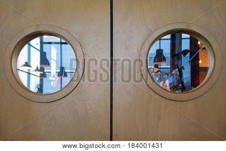 Double wooden door with round windows in modern restaurant, close up
