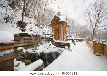 Wooden old-style structure and fountain in Russian Orthodox Monastery at winter
