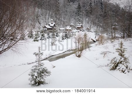 Wooden buildings and brook in Russian Orthodox Monastery at winter day among forest