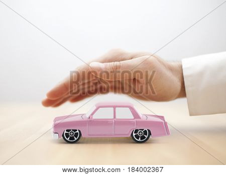 Classic old pink car toy covered by hand
