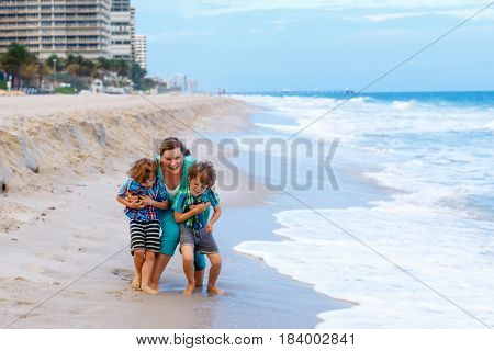 Two happy little kids boys and mother having fun on the beach of ocean and on stormy day. Family, mum and cute sons playing and making vacations and enjoying summer in Florida, Miami