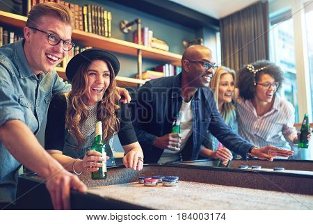 Mixed Race Friends Playing Game At Bar
