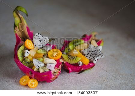 Fruit salad served in half a dragon fruit copy space
