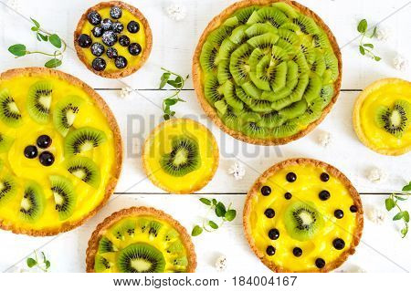 Tartlets tartas from custard kiwi and black currant of different sizes on a white wooden background. The top view.