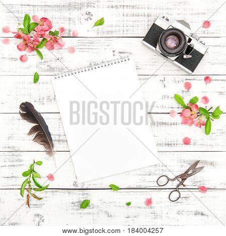 Sketchbook photo camera pink spring flowers on white wooden background. Floral flat lay