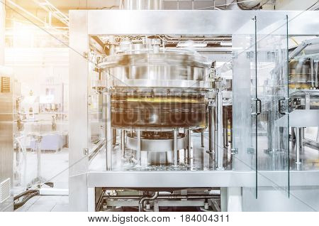 The filling machine pours beer into plastic PET bottles. Brewing production, abstract industrial background. Sunlight effect
