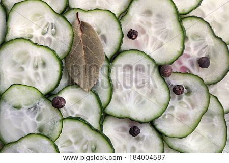 Close up ingredients for pickling - fresh cucumber slices bay leaf and pepper. Suitable for an abstract background.