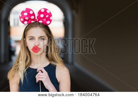 Fun party Funny pretty girl or young woman teenager with long blond hair posing with cute mouse ears and paper red lips. Decorative props on stick. Holiday birthday anniversary celebration