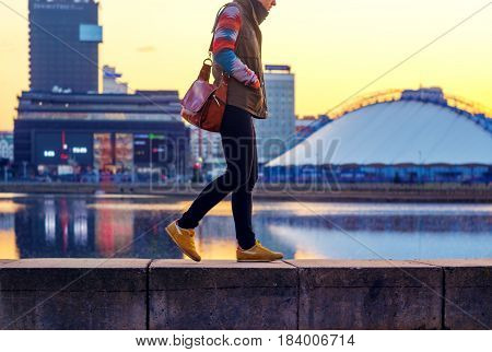 Young woman walking along the embankment in the city at sunset time. Hurry up concept