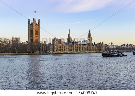 View of the tower of Big Ben and parliament buildings across the Thames river in Westminster London. Photo taken on the 21st of March while buildings are being renovated.