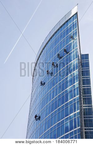 Window washers work on a skyscraper building industrial alpinism