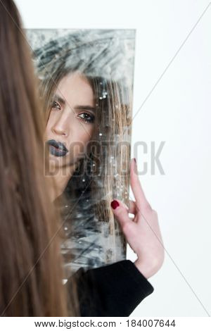 sensual young lady with long hair and fashion makeup looking and holding dirty blemished mirror with black lipstick on lips and red manicure isolated on white copy space