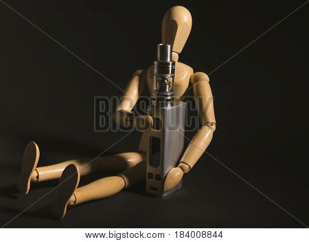 Wooden Figure Holding An Electronic Cigarette.