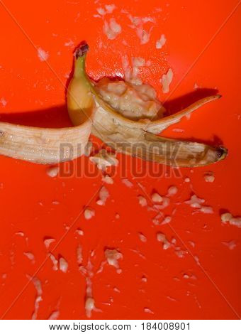 Ripe mellow banana fruit squeezed mashed or crushed with yellow skin and flesh drops splashes on bright orange background. Vitamin and healthy eating