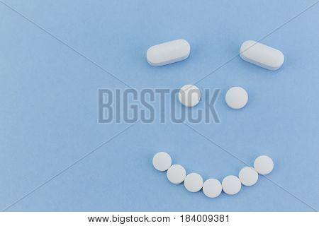 upset face made by pills on blue background