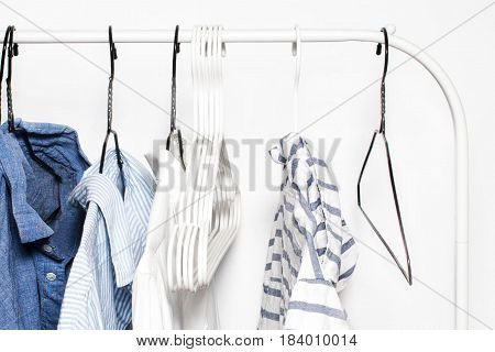 Pastel Color Clothes on Cloth Rail over white Wall Background close up with copyspace. Blue White and Stripped t-shirts