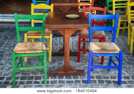 Alfresco outdoor cafe with multicolored chairs on the sidewalk street, Crete, Greece.