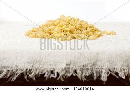 A heap of macaroni on a sacking on a light background. Photo in a rustic style composition in the center.