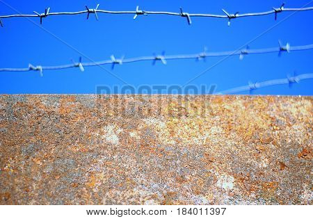 The barbed wire is taut over the prison wall. close up. Preventive measure of safety from escaping prisoners.