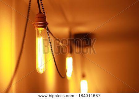 Vintage Edison lamp illuminates the room. close up