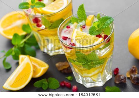 Lemon mojito cocktail with fresh mint and pomegranate cold refreshing summer drink or beverage with ice