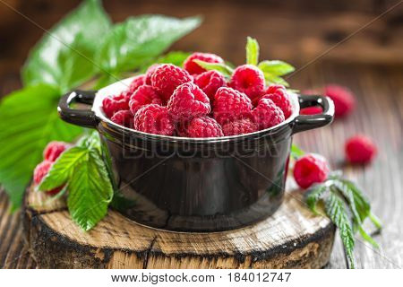 Fresh raspberry with leaves on wooden table