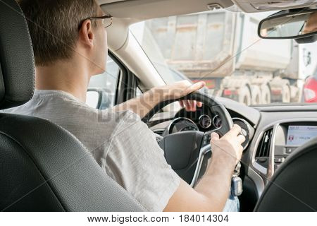 Young man driving to work, view over the shoulder. Man driving a car in tube. Generic photo of man driving a car through slight
