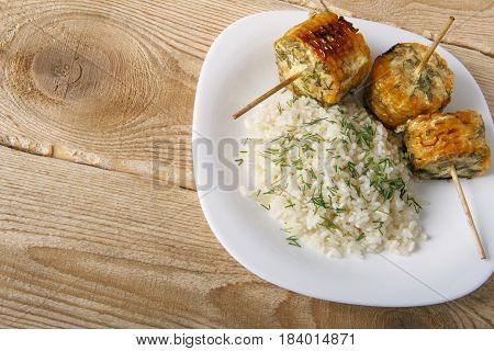 Corn cobs cooked on a grill on a wooden background. Corncobs on wooden skewers with rice