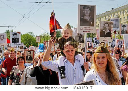 Volgograd Russia - May 09 2016: A girl in military uniform with flag sits on shoulders of her grandfather in the action