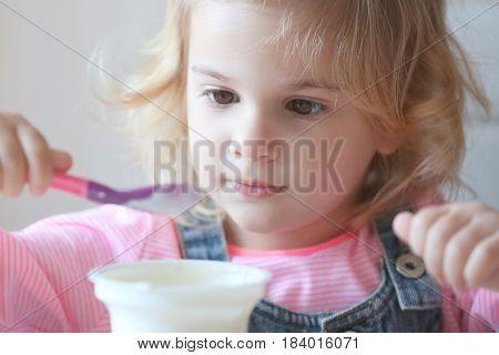 Cute little girl eating yogurt at home, closeup