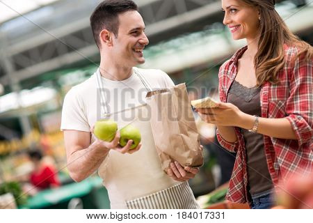 salesman and young woman looking checking list at market