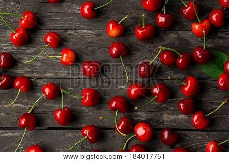 Sweet fresh cherries with water drops on wood