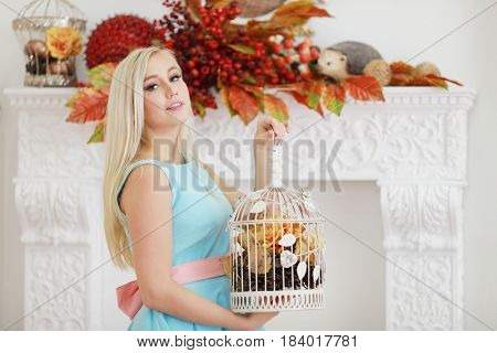 Pretty young woman in dress poses with cage with cones and dry foliage in studio